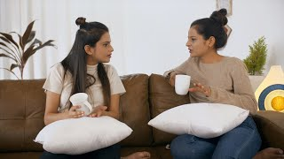 Best friends / sisters talking over a cup of coffee sitting on the couch