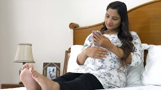 Pregnant woman texting someone using her smartphone with a smile on her face