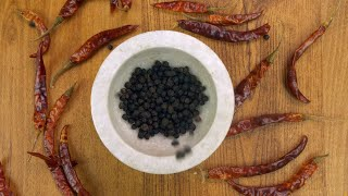 Spices of India - Closeup shot of organic black peppercorns with red dried chilies