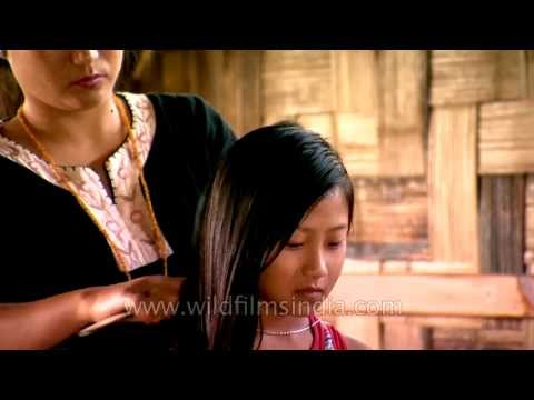 Mother fixes her hair, before Numpi goes to school in Ziro