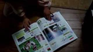 世界地図図鑑を広げて遊ぶ兄妹。 ピンクが兄で、青が妹です。 兄は数字...
