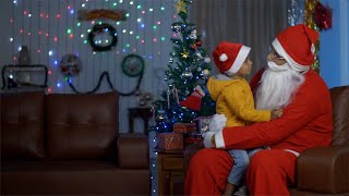 Cute little boy talking to Santa Claus while sitting in his lap on Christmas in India