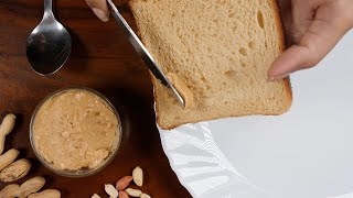 A girl spreading peanut butter over the top of a brown bread