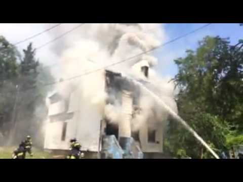 Firefighters battled Friday's extreme heat and low water pressure along with heavy fire and smoke in a vacant Paterson house blaze.