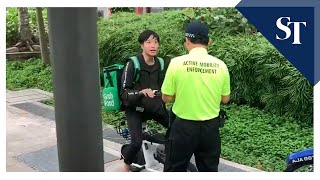 Active Mobility Enforcement officers approach PMD riders riding electric scooters on footpath
