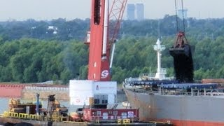 Big crane scoops huge loads of coal from a barge