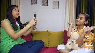 Younger and older sisters happily spending time taking pictures at home - leisure concept