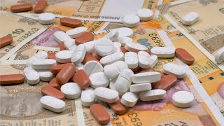 A heap of mixed medicine pills kept on a table with Indian currency (Rupee)