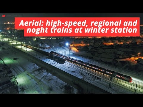 Aerial video: High-speed, long-distance and regional trains at night station in Russia
