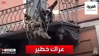 مقطع خطير لزوجين روسيين يسقطان من شرفة منزلهما بعد انهيارها خلال عراكهما