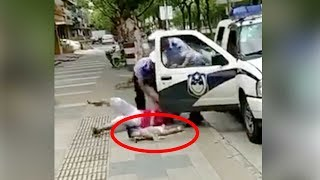 Policeman throws woman holding a baby to the ground