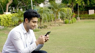 Attractive Indian guy happily using his smartphone while sitting alone in a park