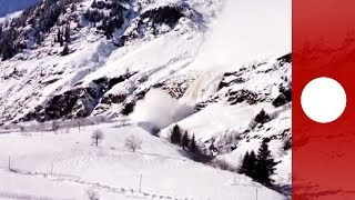 Giant avalanche creeps down Italian alps, narrowly missing houses caught on camera