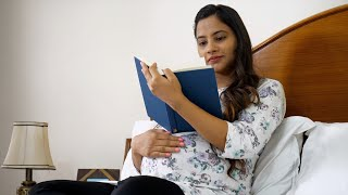 Pregnant Indian female smiling and enjoying literature while lying in her bed