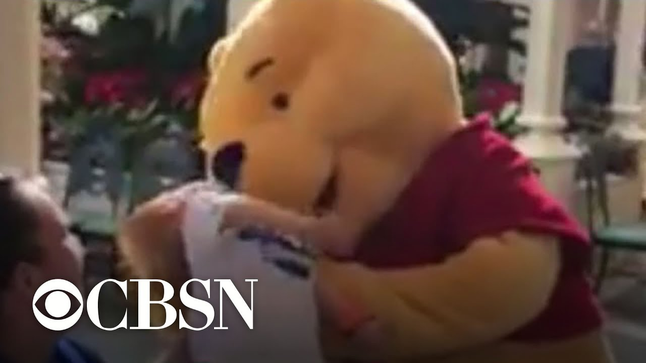 Child with special needs comforted by Winnie the Pooh at Disney World