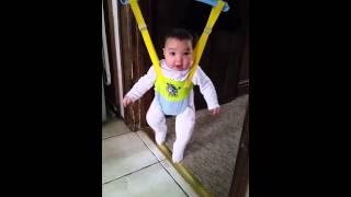 Happy 5 months old baby Ollie in a door bouncer