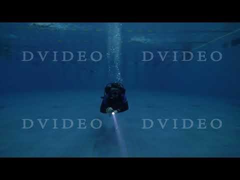 Scuba diver using underwater light during training on diving lesson in deep pool