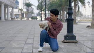 A young handsome guy playing with his cute puppy in the Indian city streets