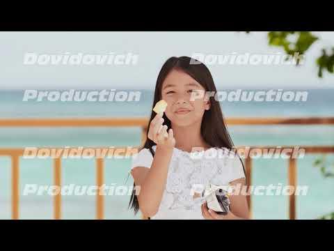 Philippine schoolgirl in white dress smiles, eating crispy potato chips. Tropical landscape. The