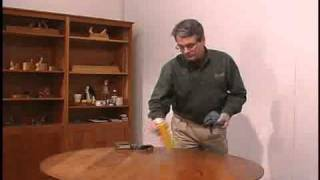 Applying a wax polish  to wood furniture to restore the luster and add a protective film