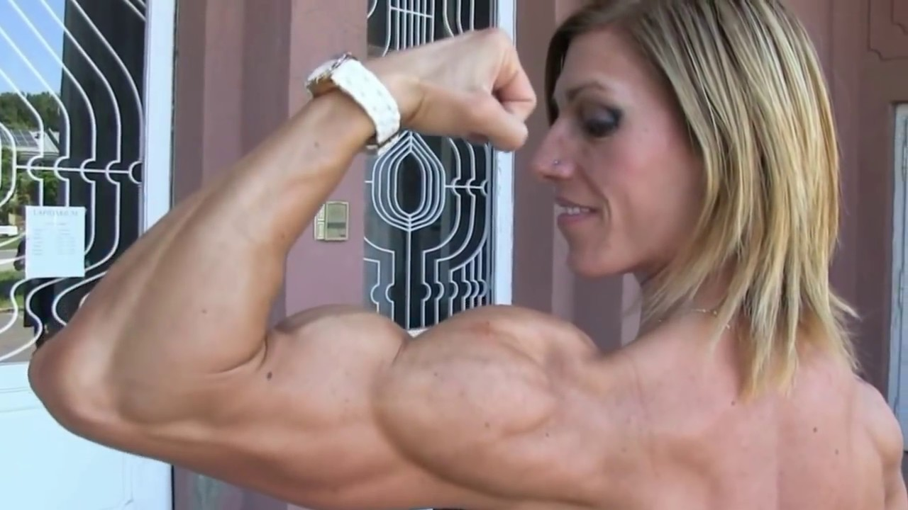Full Height Of Smiling Sports Woman Flexing Biceps And Looking