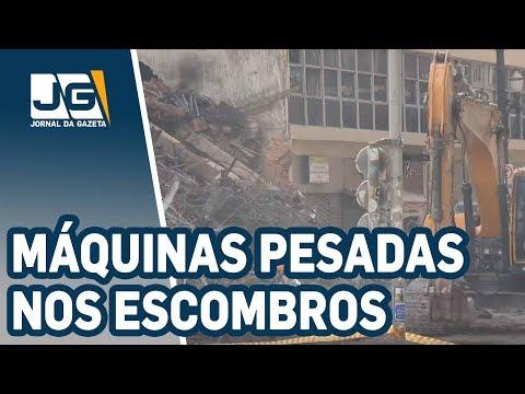Bombeiros usam máquinas pesadas nos escombros