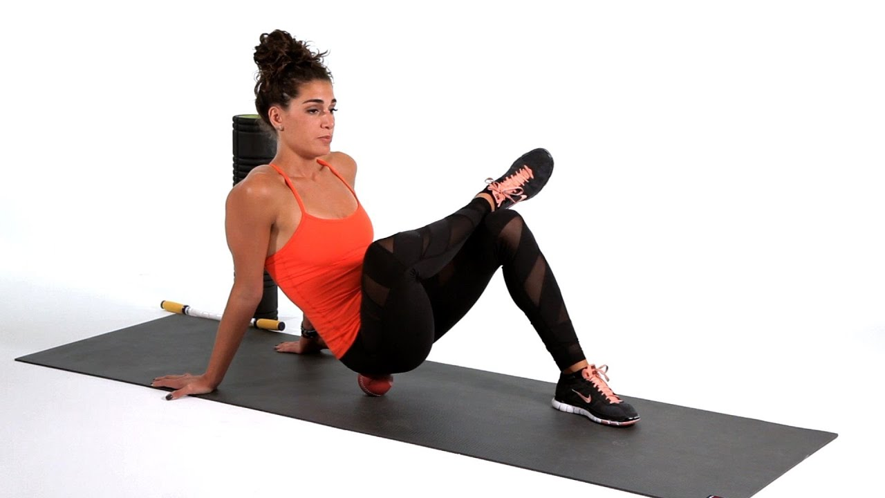 Woman on a ball doing SMR to loosen her sore muscles