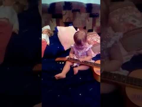 Доча Лиля играет на гитаре, год и 3 месяца.