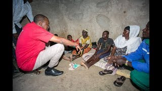 Uhuru sits on the Ground and talks to a Poor Grandmother then he Electrifies her House.