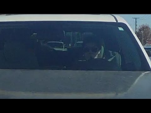 Woman looks at her phone, not the road