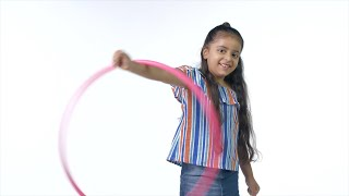 Smart Indian girl twisting hula hoop in her hand with a wide smile on her face