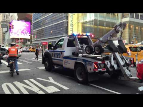 NYPD TOW TRUCK TOWING A CAR ON 8TH AVENUE IN THE HELL'S KITCHEN AREA OF MANHATTAN IN NEW YORK CITY.