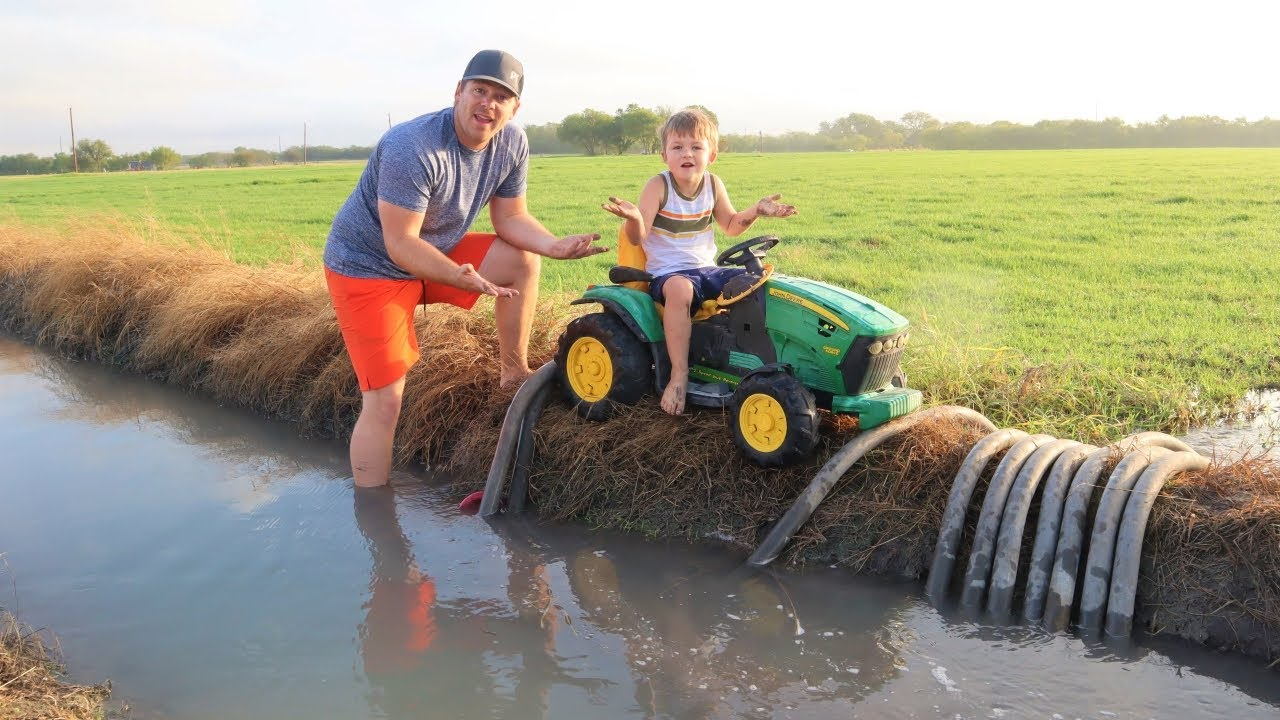 Playing in the mud and watering hay with tractors   Tractors for kids in the mud