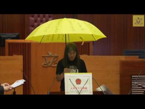 "Leung Kwok-hung ""Long Hair"" takes his oath whilst holding a yellow umbrella in protest"
