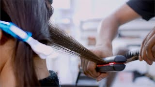 Professional male hairdresser straightening his client's hair - hairstyle concept