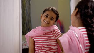 Young Indian child girl wearing pink dupatta in front of a mirror at home - Dressing like her mother