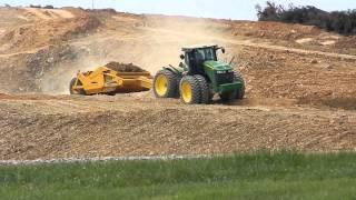John Deere tractor and pan moving dirt.