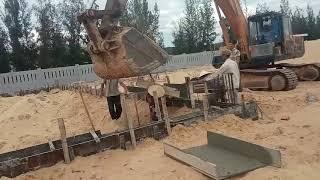 Máy xúc đào lấy bê tông từ xe trộn