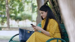 Beautiful young woman with long hair chatting on her smartphone - lifestyle concept