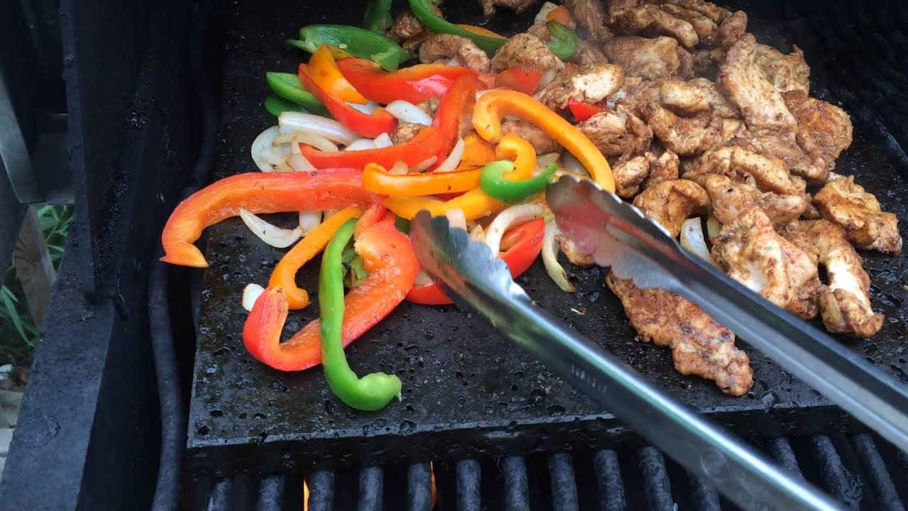 Grilling Chicken Peppers And Onions On The Island Grillstone For Fajitas