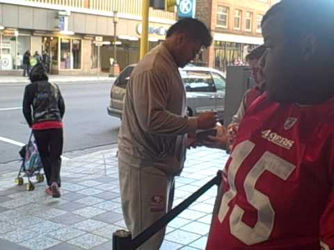 Mike Iupati of The San Francisco 49ers signing autographs