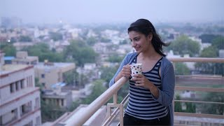 Carefree happy Indian girl drinking coffee / tea while standing in her room balcony