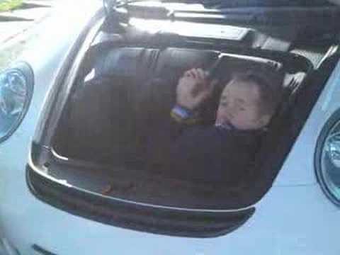 Vicki Butler Henderson showing the boot space of a Porsche