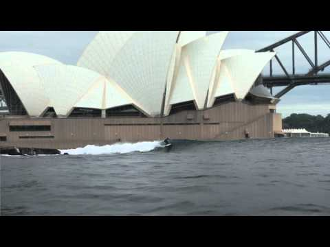 It's still fake: Surfers ride waves in Sydney Harbour after wild storm