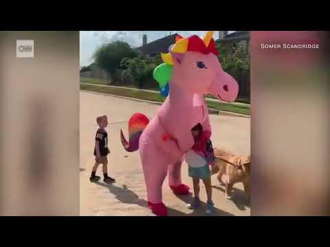 None - Mom dresses up as unicorn to surprise daughter at bus stop