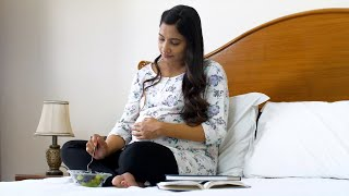Pregnant Indian woman eating a bowl full of fresh fruits while sitting in her bed