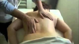Врач делает лечебный массаж спины