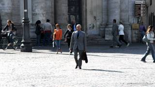 Business man walking through a plaza in Rome Italy.