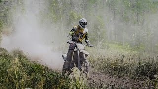 racer motorcyclist rides along dusty forest trail