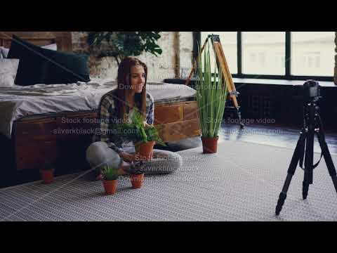 Young woman famous blogger is recording video about pot flowers using camera while sitting on